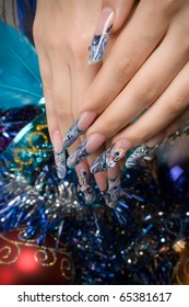 Hand of the woman with the French manicure c New Year's toys
