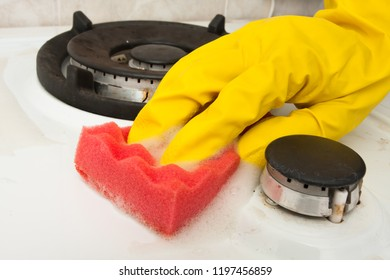hand of woman in glove cleaning gas cooker in the kitchen