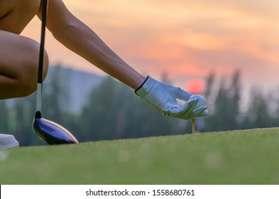 Hand of woman golfer laying golf ball onto wooden tee on tee off in the golf course with sunset light in background