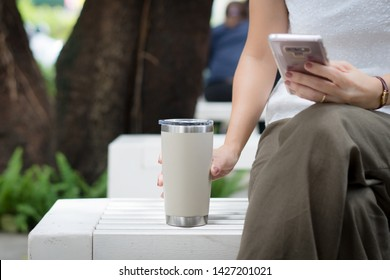 Hand of a woman grabbing reusable coffee cup, tumbler while texting message in her smart phone. Environmental friendly, eco living, No one-time use plastic, No straw, Urban leisure, Zero waste concept