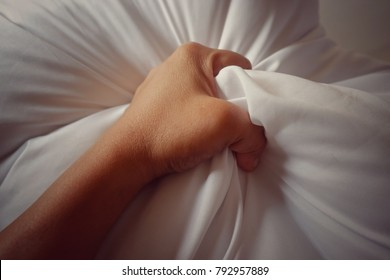 The hand of a woman gripping on a blanket, vintage white, soft focus.