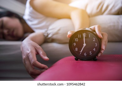 Hand woman hates getting stressed waking up early,Female stretching her hand to ringing alarm to turn off alarm clock