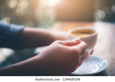 Hand of woman hold coffee or coffe cup at cafe in the morning