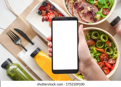 Hand of woman hold phone mock up white screen over weight loss diet fresh healthy food take away boxes bag daily nutrition ready menu plan meal online delivery service mobile app ad. Flat lay top view