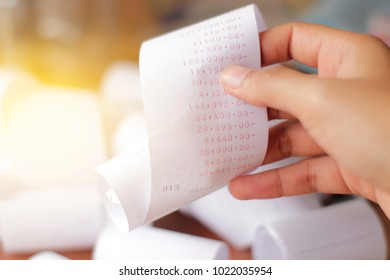 hand of woman holding a bill for income and expenditure with soft focus