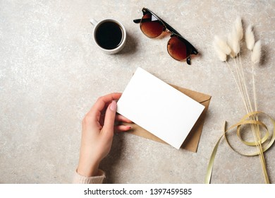 Hand of woman holding blank paper card over feminine desk with hipster accessories, sunglasses, coffee cup and dry flowers. Flat lay, top view home office table. Social media hero header background