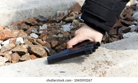 The hand of a woman holding a gun.