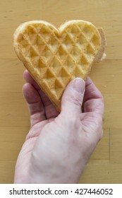 Hand of woman holding heart shaped waffle