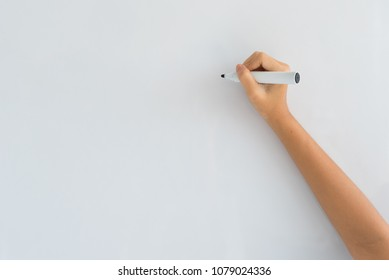 The hand of a woman holding a marker ready to write something on a white board.