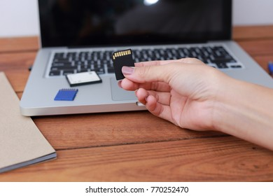 hand woman holding memory card with laptop background. Closeup.