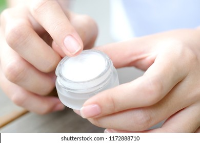 Hand of woman holding moisturizer cream and serum. She applying a facial cream , essential , oil , lotion and body cream for skin care, close up view and blur background. Beauty and Healthy Concept.