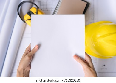 Hand of woman holding papers on desk engineer in office. top view with copy space.