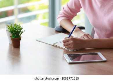 Hand of a woman holding a pencil writing for work.