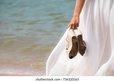 The hand of a woman holding a shoe and walking on the beach.