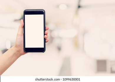 Hand woman holding and showing phone with blurred background in shopping mall.