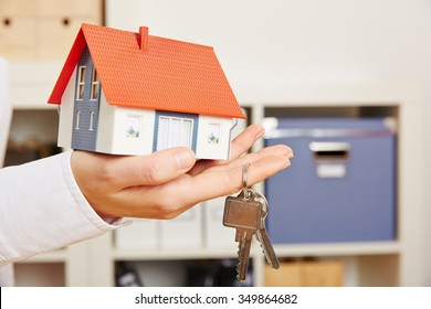 Hand of a woman holding a small house with two keys