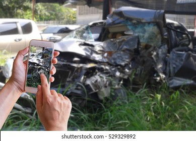 Hand of woman holding smart phone and take photo of the car accident