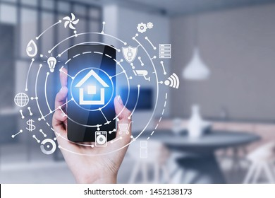 Hand of woman holding smartphone in blurred kitchen with double exposure of smart home interface. Concept of automation.