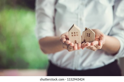 Hand of woman holding a toy house. Home safety , Home care , Home for sale concept.