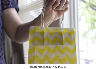 Hand of woman holding yellow chevron paper shopping bag