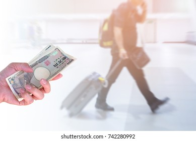 hand woman with Japanese currency yen bank notes on blurred background travelers walking with a luggage at airport terminal, travel cost