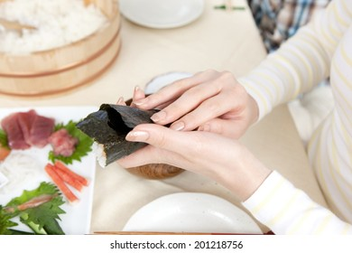 Hand of a woman making a hand-rolled sushi