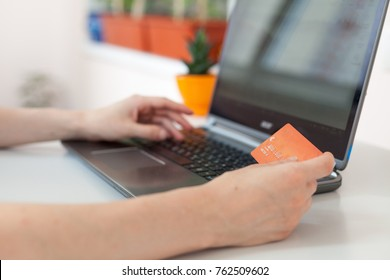 Hand of a woman making purchases through the Internet. Online Shopping. Focus on the hand and on the card. Paying with credit card online