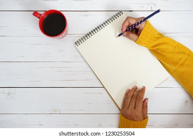 Hand of woman in mustard yellow sweater holding polka dot pencil to write some text or messages on blank white writing paper space e.g. Merry Christmas, New Year's Resolutions, To Do or Wish List 2019