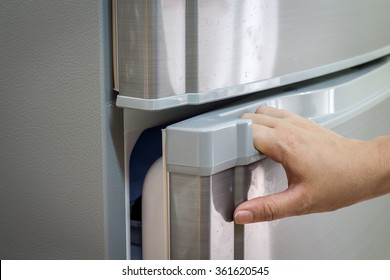 Hand a woman is opening a refrigerator door