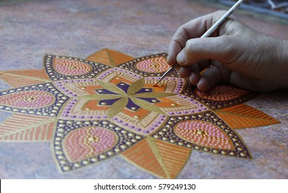 Hand of a woman painting a mandala dot painting style