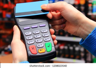 Hand of woman paying with contactless credit card with NFC technology in shop, cashless paying for shopping or products concept