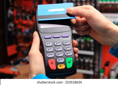 Hand of woman paying with contactless credit card with NFC technology in an electrical shop, credit card reader, payment terminal, finance concept