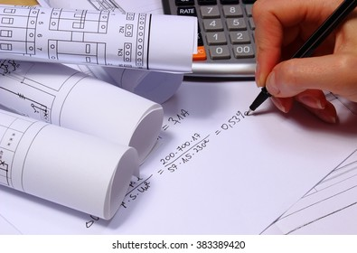 Hand of woman performing mathematical calculations for project, rolls of electrical diagrams, drawings for the projects engineer jobs