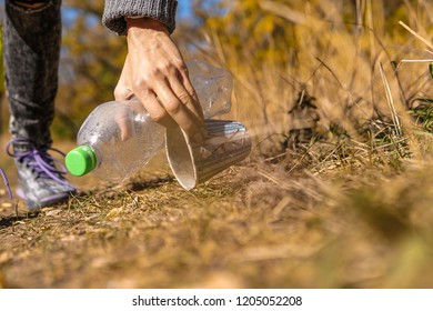 Hand woman picking up plastic bottle cleaning in the street, in forest, volunteer concept