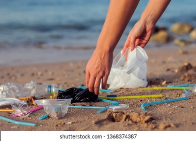 Hand woman picking up plastic bottle cleaning on the beach. Environmental pollution concept