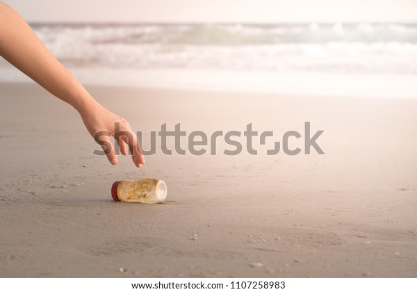 The hand of a woman is picking up a plastic bottle to clean the beach.