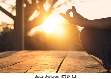 Hand of woman practicing meditation yoga on the nature at sunset