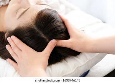 The hand of the woman and the practitioner who receives the scalp massage