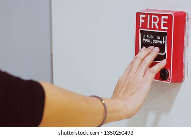 Hand of woman pulling fire alarm on the wall for test notifier system.