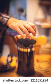 Hand of a woman pushing a coffee maker. The bokeh is uneasy an is looking nervous.