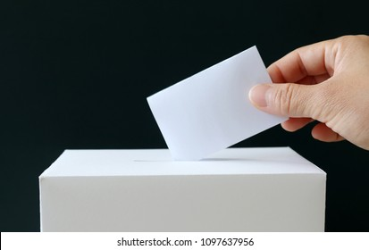 The hand of a woman putting a ballot in the ballot box. Close-up image of ballot and the ballot box.
