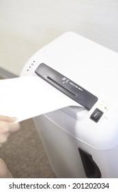 a hand of woman putting a paper through a Schrotter