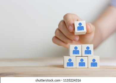 Hand woman putting wood cube block on top pyramid,Human resources, social networking, assessment center concept, personal audit or CRM concept - recruiter complete