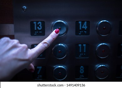 The hand of a woman with red fingernails presses the Number 13 on the elevator. Many elevators leave this number out due to beliefs that it is unlucky.