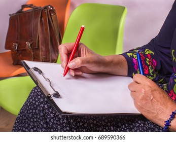 Hand of woman with a red  pen ready to write on paper.