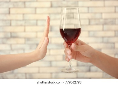 Hand of woman refusing glass of alcohol against brick wall