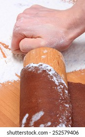 Hand of woman with rolling pin kneading dough for Christmas cookies and gingerbread, concept for baking