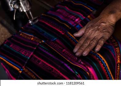 Hand of woman sewing Guatemalan fabric