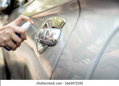 Hand of woman is spraying alcohol,disinfectant spray on handle of car door,safety,prevent infection of Covid-19 virus,contamination of germs or bacteria,wipe clean surfaces that are frequently touched