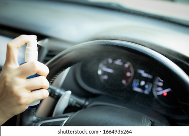 Hand of woman is spraying alcohol,disinfectant spray on steering wheel in her car,prevent infection of Covid-19 virus,contamination of germs or bacteria,wipe clean surfaces that are frequently touched - Shutterstock ID 1664935264